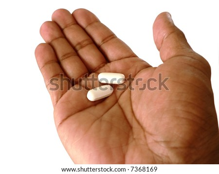 two aspirin in a open hand to be taken to relieve pain. isolated over white background by clipping path
