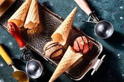Two assorted flavors of Ice-cream, wafer cones or cornets and scoops in a top down still life on a tray