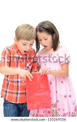two astonished children looking into a shopping bag