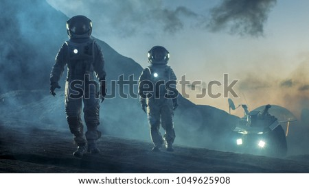 Two Astronauts in Space Suits Confidently Walking on Alien Planet, Exploration of the the Planet's Surface. In the Background Research Base/ Station and Rover. Space Travel, Colonization Concept. #1049625908