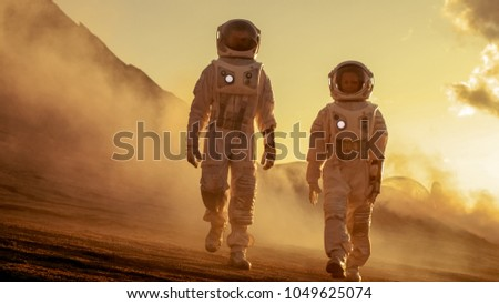 Two Astronauts in Space Suits Confidently Walking on Mars, Exploration Expedition on the Planet's Surface. Red Planet Covered in Rocks, Gas and Smoke. Humans Overcoming Difficulties. #1049625074