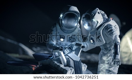 Two Astronauts in Space Suits on an Alien Planet Prepare Space Rover for Planet\'s Surface Exploration Expedition. Space Travel and Solar System Colonization Concept.