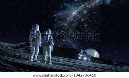 Two Astronauts in Space Suits Stand on the Planet and Looking at the The Milky Way Galaxy. In the Background Lunar Base with Geodesic Dome. Moon Colonization and Space Travel Concept. #1042736410