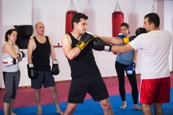 Two athlete men in sportswear exercising boxing sparring at sport class