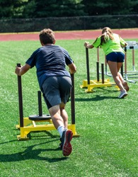 Two athletes pushing heavy yellow sleds across a green turf field during track and field strenth and agility practice.