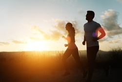 Two athletes running at sunset. Backlit silhouette of man and woman training together.