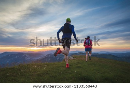 Two athletes trailrunning in the hills during sunset. Shallow D.O.F.