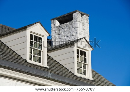 Two Attic Windows Stick Out From A Colonial Roof Stock
