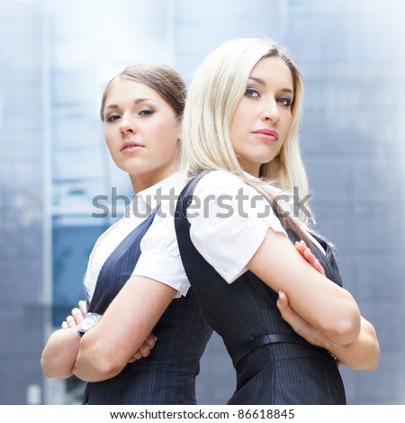 Two attractive business women over modern street background - stock photo