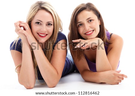 Two attractive cheerful women relaxing on the floor lying side by side on their stomachs sharing a moment of companionship