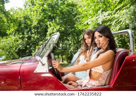 Two attractive fashion girlfriends driving red convertible stock photo