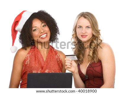 Two attractive females (one ethnic in sexy Mrs. Santa Claus costume and one Caucasian blonde in red dress) browsing internet on notebook portable computer, while holding credit card in hand