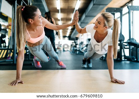 Two attractive fitness girls doing push ups #679609810