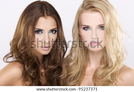 Two attractive girl friends - blond and brunette on white background
