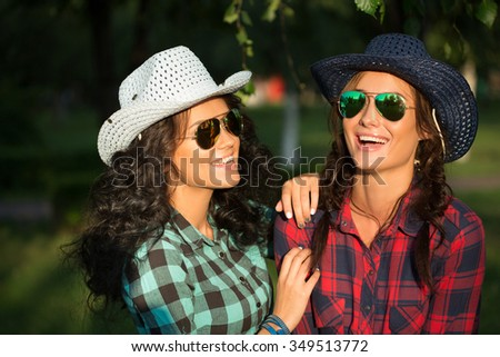 Two attractive girls in cowboy hats and sunglasses walking park. happily laughing