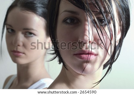 two attractive girls looking into the camera. Soft focused. Focal point is on the right face.