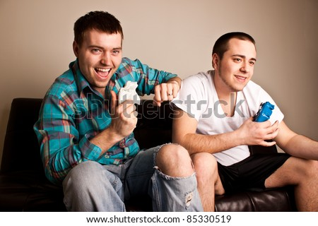 Two attractive guys having fun while playing video games