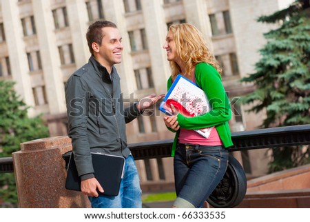 Two attractive happy students talking at campus