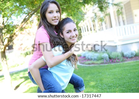 Two attractive hispanic sisters displaying the love of family at home