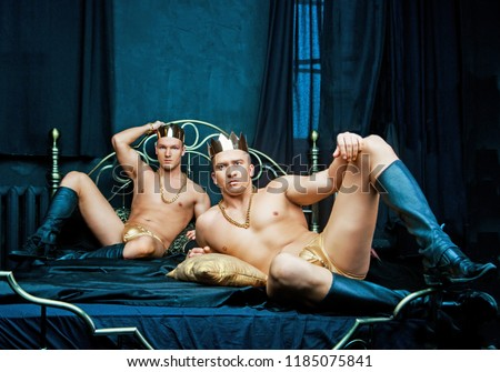 two attractive muscular men wearing crowns,  golden chains and underwear   in bed with black linen