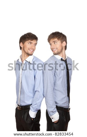 Two attractive positive smile young business people brother twins standing looking to each other, dressed in shirt, tie. Concept Success, isolated over white background