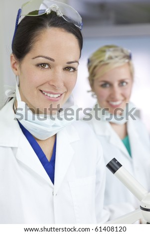 Two attractive smiling female scientists or women doctors wearing a white coats in a laboratory or hospital