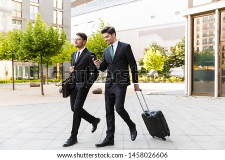 Two attractive smiling young businessmen wearing suits walking outdoors at the city streets, carrying suitcase, using mobile phone