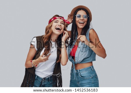 Two attractive stylish young women laughing while standing against grey background #1452536183