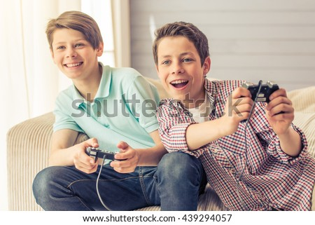 Two attractive teenage boys are playing game console and smiling while sitting on the couch at home Stock foto ©