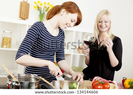 Two attractive women friends preparing a meal in the kitchen together with one chopping vegetables watched by the second who is enjoying a glass of red wine