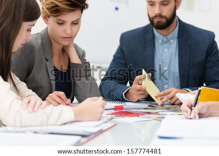 Two attractive young females business colleagues in a meeting having a discussion watched by a male coworker