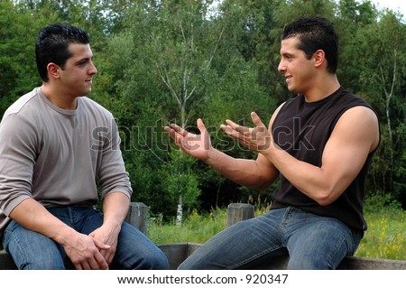 Two attractive young men, twins on their  lunch hour, taking a rest in the park, having a conversation. This is a trick photo of the same person twice.