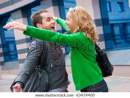 Two attractive young people met in the street and they are happy