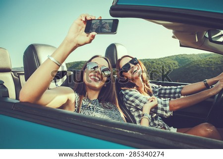 Two attractive young women dtaking selfe in a convertible car
