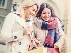Two attractive young women holding shopping bags and smiling. Consumerism and lifestyle concept