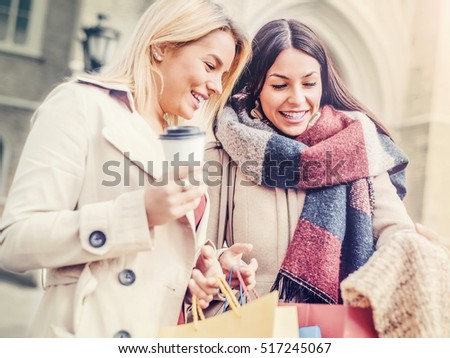 Two attractive young women holding shopping bags and smiling. Consumerism and lifestyle concept #517245067
