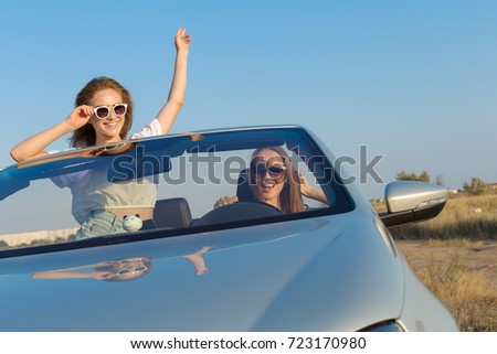Two attractive young women in a cabriolet car #723170980