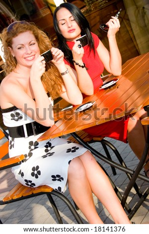 Two attractive young women in street cafe
