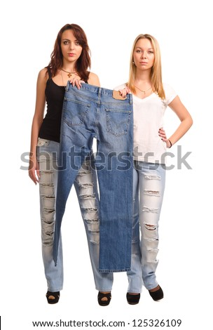 Two attractive young women standing side by side holding up a pair of blue denim jeans, studio portrait isolated on white