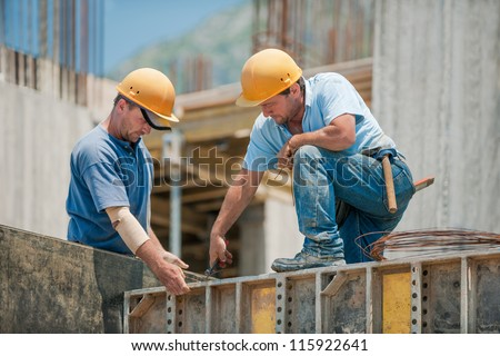 Two authentic construction workers collaborating in the installation of concrete formwork frames - stock photo
