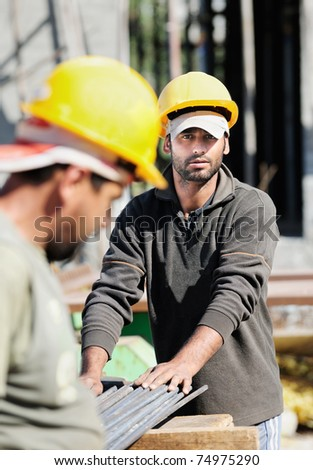 Two authentic construction workers, one of them looking at camera
