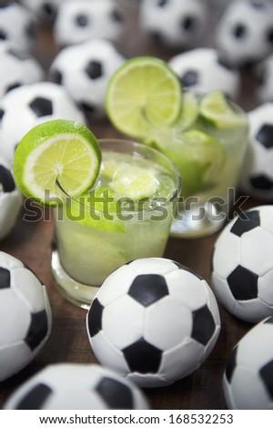 Two authentic fresh lime caipirinhas with soccer footballs Brazilian culture