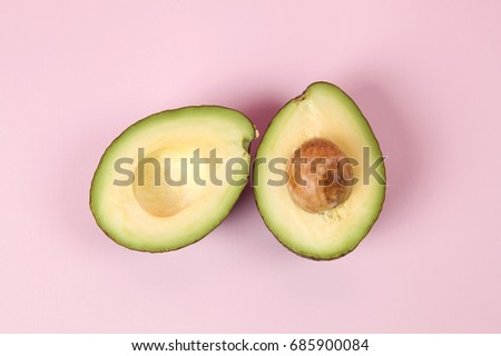 two avocado half with seed on a pink background. minimal color still life photography