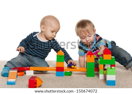 Two baby boys are playing on the carpet