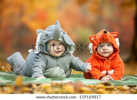 Stock Photo Two baby boys dressed in animal costumes in autumn park, focus on baby in elephant costume