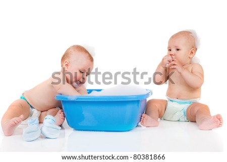 Two baby friends sit beside blue tub