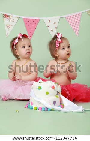 Two baby girl identical twin sisters sitting on green seamless background behind decorated birthday cake wearing red and pink tutus and bunting flags in the background about to break and smash cake