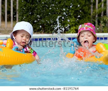 Two baby girls splashing water in a pool