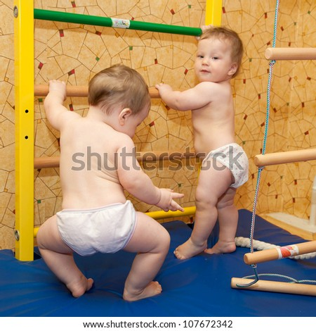 Two baby twins playing sports and climbing the stairs. A healthy lifestyle from infancy