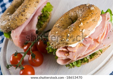 Two bagels with honey roasted ham on a wooden board
